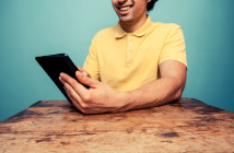 Young man at table reading on tablet