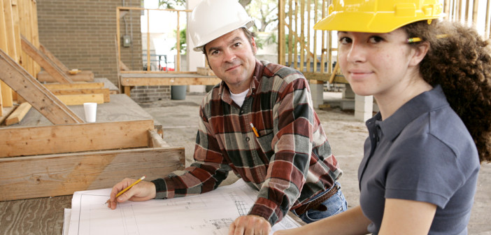 A construction foreman going over the blueprints with a female apprentice.