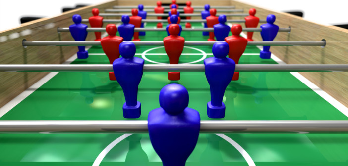 A perspective view of a wooden foosball table showing a blue and red team on a green marked pitch on an isolated white background
