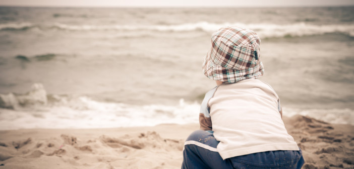 Boy sitting on beach alone looking out to sea