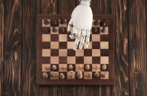 Robotic hand on chess board moving a piece