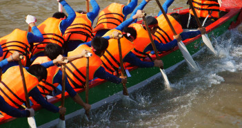 Team building activity on water, group of strong, active man rowing dragon boat racing, they try to row with high speed and championship spirit, rhythm of paddle so dynamic