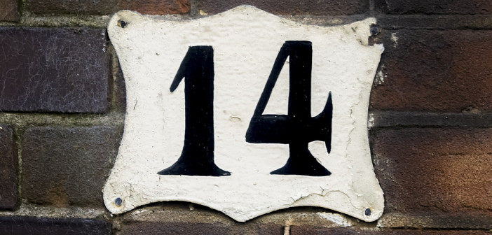 house number fourteen on a brick wall.