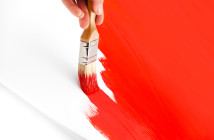 Brush painting red paint.