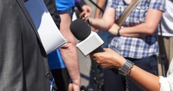 Person being interviewed in street by journalist.
