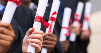 A group of graduates holding diploma