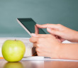 Student using digital tablet beside green apple while studying