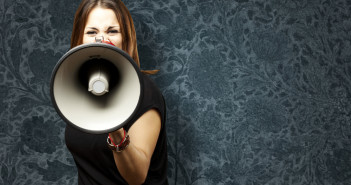 portrait of young woman shouting with megaphone