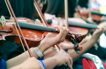 Hands of violinists playing violins outdoor