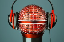 a single microphone with headphones on dark background, a speak and listen music concept