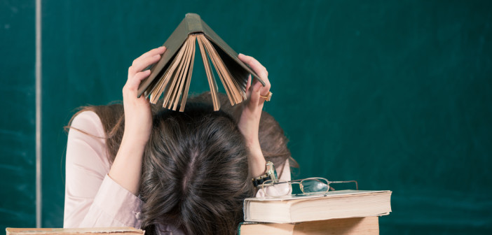 Teacher surrounded by books with head down