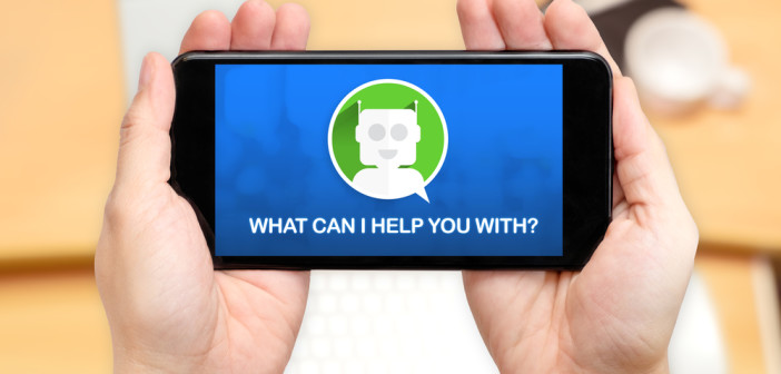 Watching two hand holding mobile phone with Chat bot and what can i help you with? with blur desk office background
