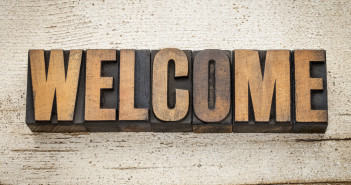 welcome word in vintage letterpress wood type on a grunge painted barn wood background