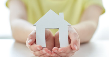 close up of happy girl holding paper house cutout in cupped hands