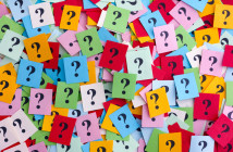 Pile of colorful paper notes with question marks.