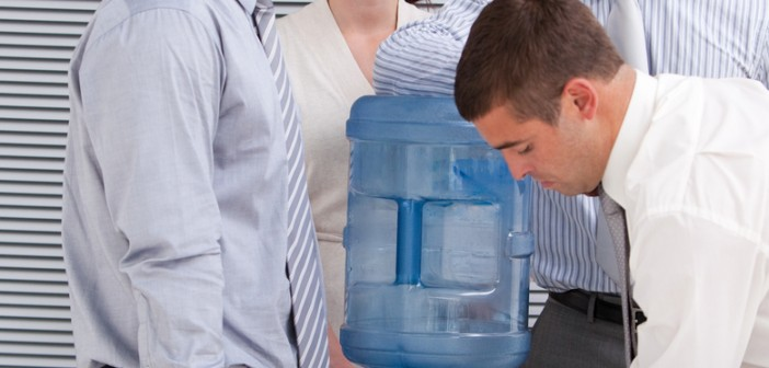 business people interacting at a watercooler in the office
