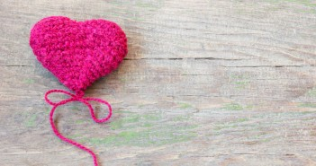Knitted pink heart on a wooden background