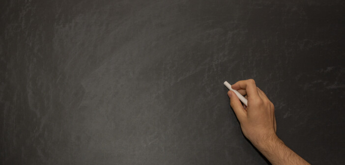 hand writing with white chalk on black chalkboard