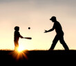 silhouette of a father and his young child playing baseball outside, isolated against the sunsetting sky on a summer day.