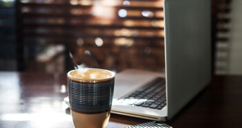 Coffee cup and laptop at home